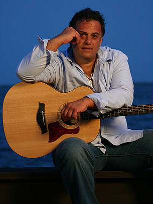 Front facing photo of Michael Rainwood, seated with his guitar